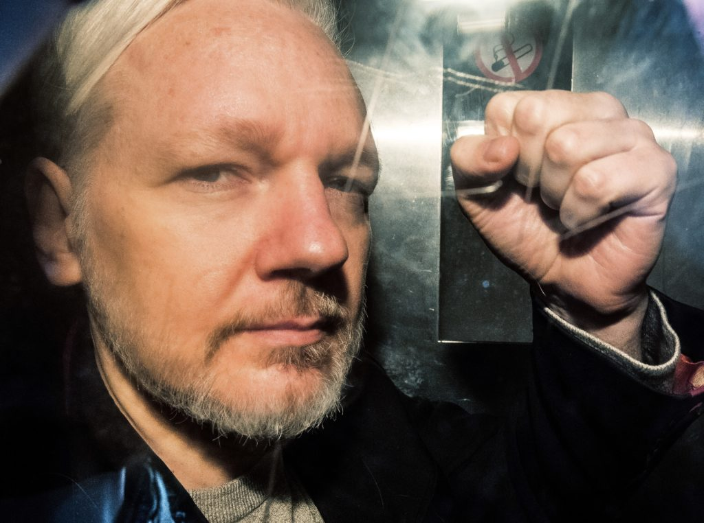 WikiLeaks founder Julian Assange gestures from the window of a prison van as he is driven into Southwark Crown Court in London on May 1, 2019, before being sentenced to 50 weeks in prison for breaching his bail conditions in 2012. - A British judge on Wednesday sentenced WikiLeaks founder Julian Assange to 50 weeks in prison for breaching his bail conditions in 2012. Assange took refuge in Ecuador's London embassy to avoid extradition to Sweden and was only arrested last month after Ecuador withdrew his asylum status. (Photo by Daniel LEAL-OLIVAS / AFP)